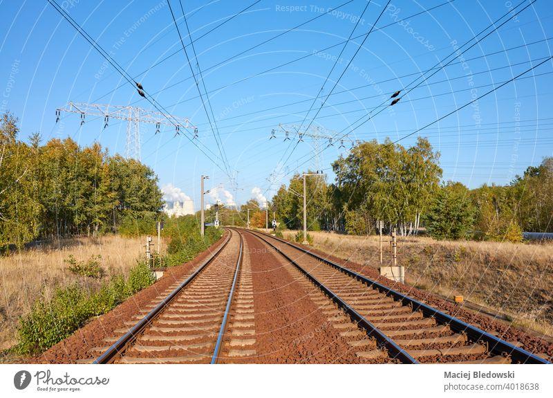 Eisenbahn mit Kraftwerk und Hochspannungsfreileitung im Hintergrund. reisen Eisenbahngleis Transport Landschaft Industrie Energiezentrum Wald Verkehr Bahn