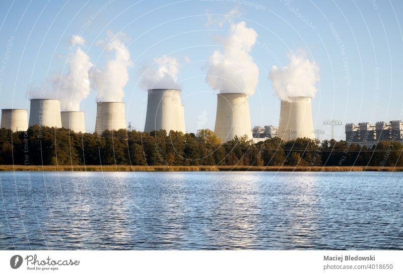 Kraftwerk mit rauchenden Schornsteinen an einem See bei Sonnenuntergang. Industrie Energiezentrum Pflanze Rauch Verschmutzung dreckig Station Umwelt Gebäude