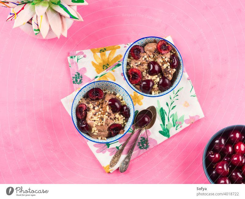 Schokoladeneis mit Streuseln, Nüssen und frischen Kirschen auf rosa Eis Sahne Eisbecher Vanille Dessert Glas Schalen & Schüsseln Lebensmittel Nut Baggerlöffel