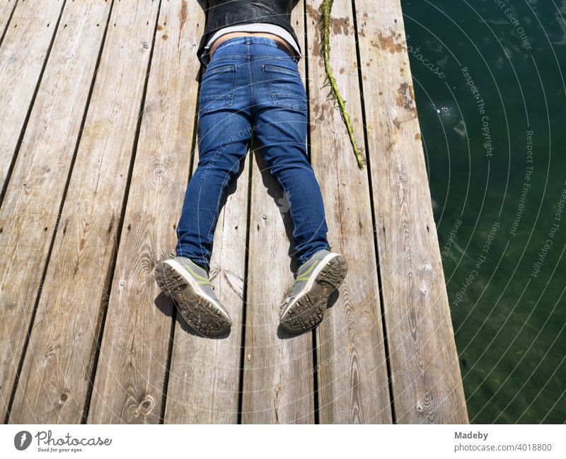 Junge in blauen Jeans auf einem Bootssteg aus rustikalem Holz am Lippesee im Sommer in Paderborn in Ostwestfalen-Lippe Holzsteg Badesteg Blue Jeans Steg