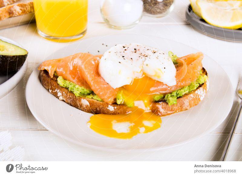 Vollkornbrottoast, zerdrückte Avocado, Lachs und pochiertes Ei Frühstück gekocht Zuprosten Brot grün Entzug Diät Zitrone Clementine Fisch Saft Glas Tasse