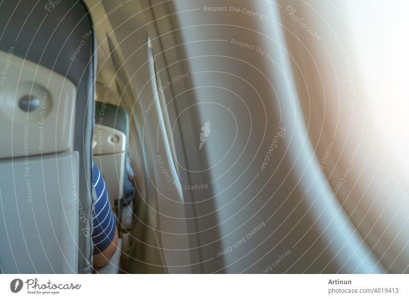 Rückansicht von Flugzeugsitz in der Nähe von Flugzeugfenster. Economy-Klasse-Flugzeug. Innerhalb der kommerziellen Fluggesellschaft. Kleiner Raum zwischen Passagier Economy Sitz und Fenster des Flugzeugs. Sitz mit Sessel. Ledersitz.