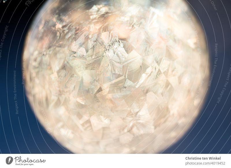 gefrorene Seifenblase an einem wunderbaren eiskalten und sonnigen Wintermorgen im Gegenlicht der tiefstehenden Sonne Eisblase strenger Frost Eiskristalle