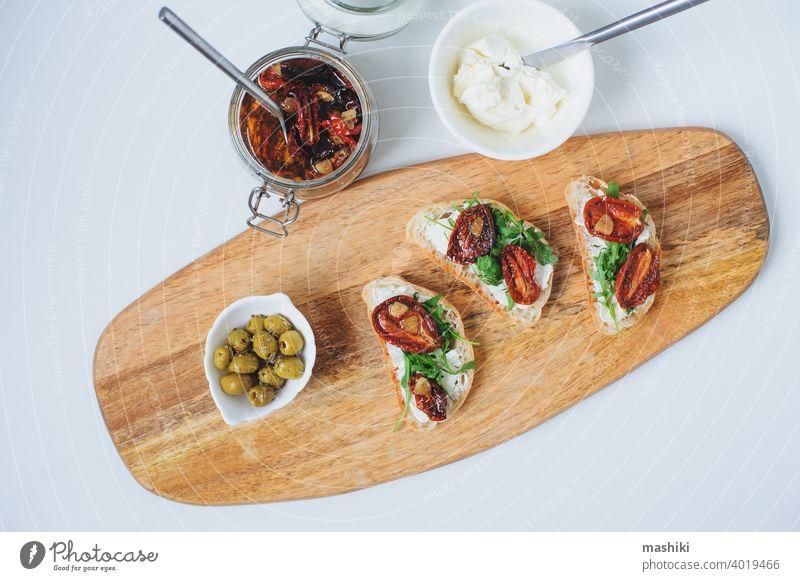 traditionelle italienische Bruschetta - Brottoast mit sonnengetrockneten Tomaten, Frischkäse, Olivenöl und Rucola. Belegtes Brot Lebensmittel Zuprosten Snack