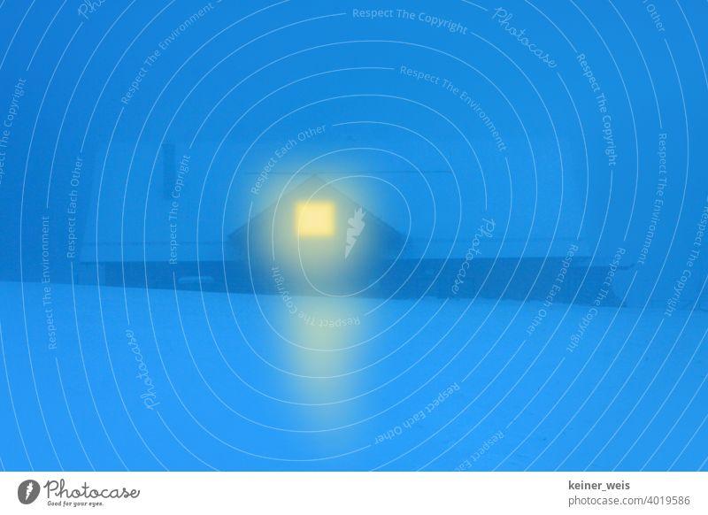 Ein warmes Licht im Fenster zeigt den Weg nach hause durch die kalte Winternacht zur blauen Stunde Haus Schnee Nacht blaue Stunde Dunkelheit verschneit Hütte
