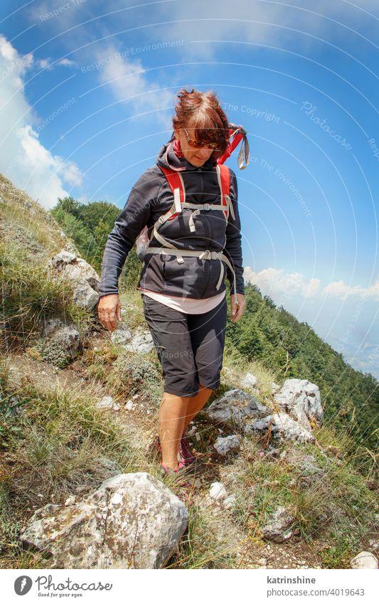 Mittleres Alter Frau Wandern in den Bergen in einem sonnigen Tag Frauen wandern Stöcke Lebensmitte Sport Natur im Freien acivity Erholung Nachlauf Person
