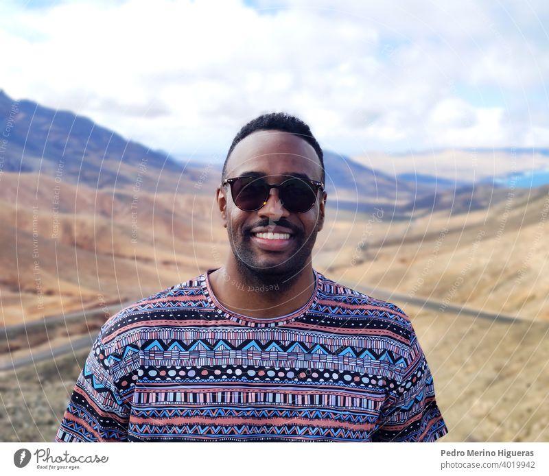 Porträt eines schwarzen Mannes in einer Ansicht von Fuerteventura. vereinzelt Straße Schönheit heiter Typ im Freien Freizeitkleidung Lächeln Person photogen