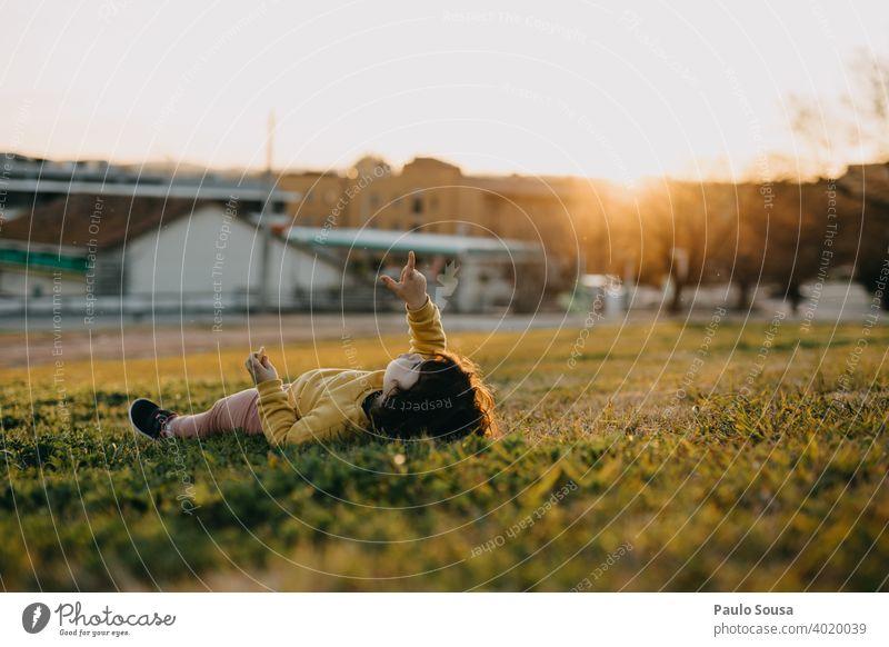 Nettes Mädchen zeigen auf den Himmel Kind 1-3 Jahre Gras Lügen Mensch Farbfoto Kleinkind Kindheit Außenaufnahme Tag Natur feminin träumen Punkt Porträt Spielen