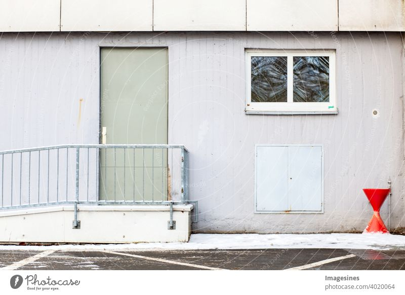 Raucherbereich.  Fassade und Aschenbecher neben der Tür außerhalb eines Gebäudes. Einsamer Außenbereich mit rotem Aschenbecher für Raucher zur Zigarettenpause vor einem Wohnhaus