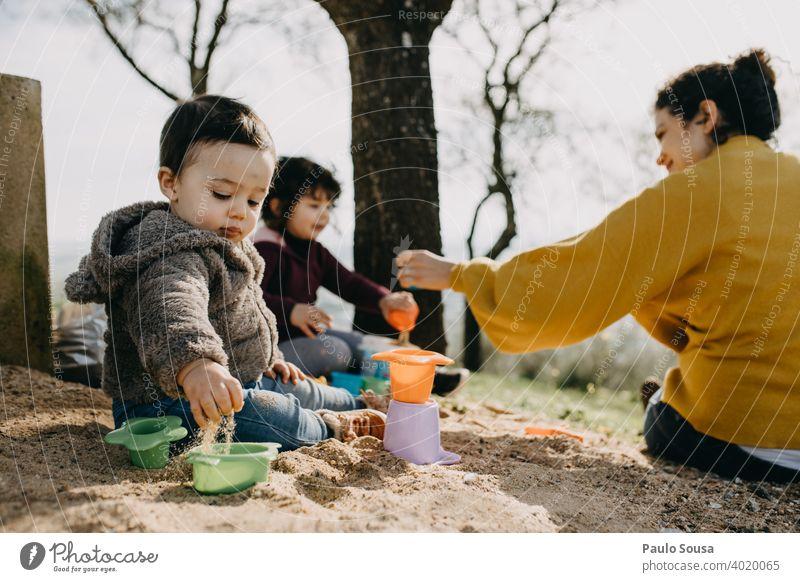 Kind spielt mit Mutter und Schwester im Freien mit Sand Kindheit Familie & Verwandtschaft Kindheitserinnerung Farbfoto Lifestyle Freude Kaukasier Fröhlichkeit