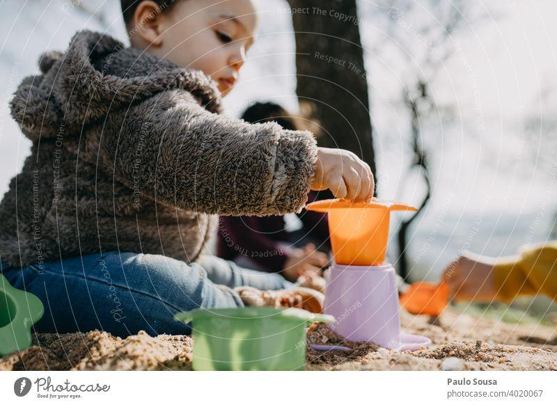 Kind spielt im Freien mit Sand Kindheit 1-3 Jahre authentisch Frühling Farbfoto Kleinkind Mensch Lifestyle Spielen Fröhlichkeit Leben Kindheitserinnerung Glück