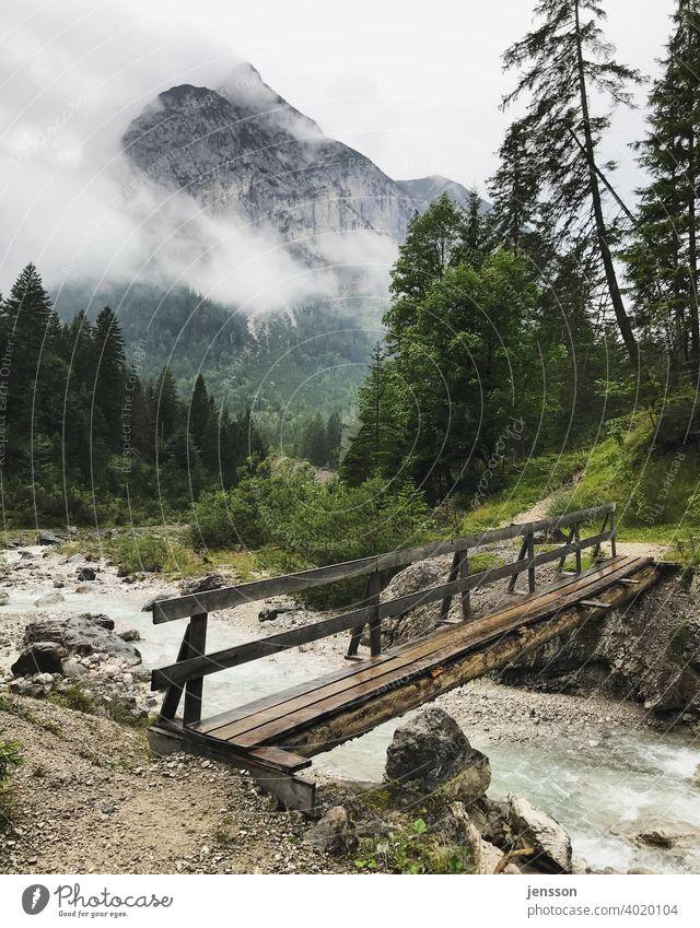 Holzbrücke über einen Wildbach im Karwendelgebirge Brücke Berge u. Gebirge Wolken Bach Tourismus wandern Österreich diesig Wetter Alpen Natur Menschenleer
