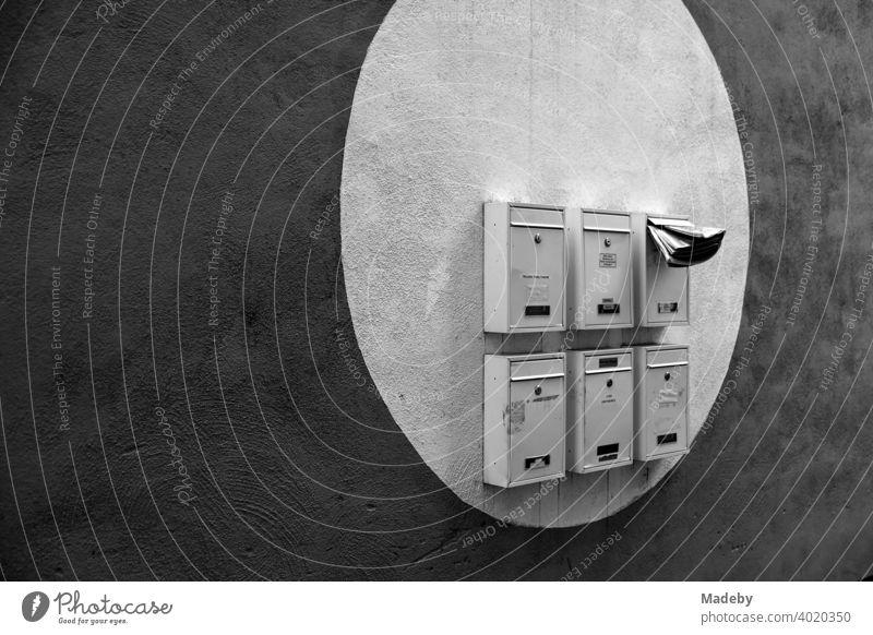 Briefkästen in einem aufgemalten hellen Kreis auf dunkler Fassade in Offenbach am Main in Hessen, fotografiert in klassischem Schwarzweiß Briefkasten Post