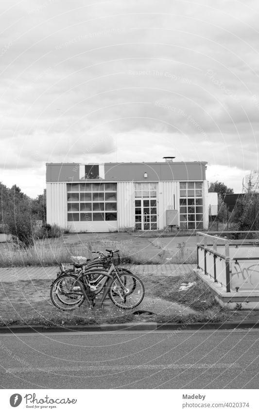 Fahrradständer mit Fahrrädern auf einem Grünstreifen in trostloser Umgebung im Gewerbegebiet an der Hanauer Landstraße in Frankfurt am Main, Stadtteil Fechenheim