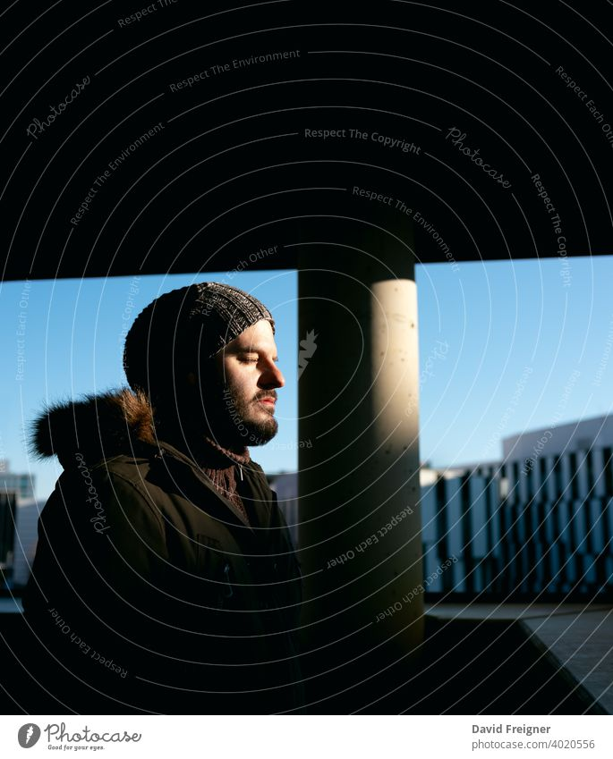 Mann steht auf einem Balkon und genießt die letzte Sonne des Tages im Winter. Urban Stadt Porträt Konzept. Sonnenuntergang Erwachsener kalt allein Typ urban 40s