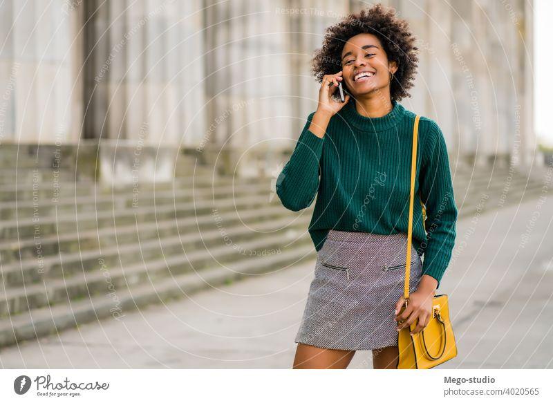 Geschäftsfrau beim Telefonieren im Freien. Afro-Look Business Frau Mobile reden modern Stil brünett Apparatur positiv Konzept Anschluss Anwendung SMS Texten
