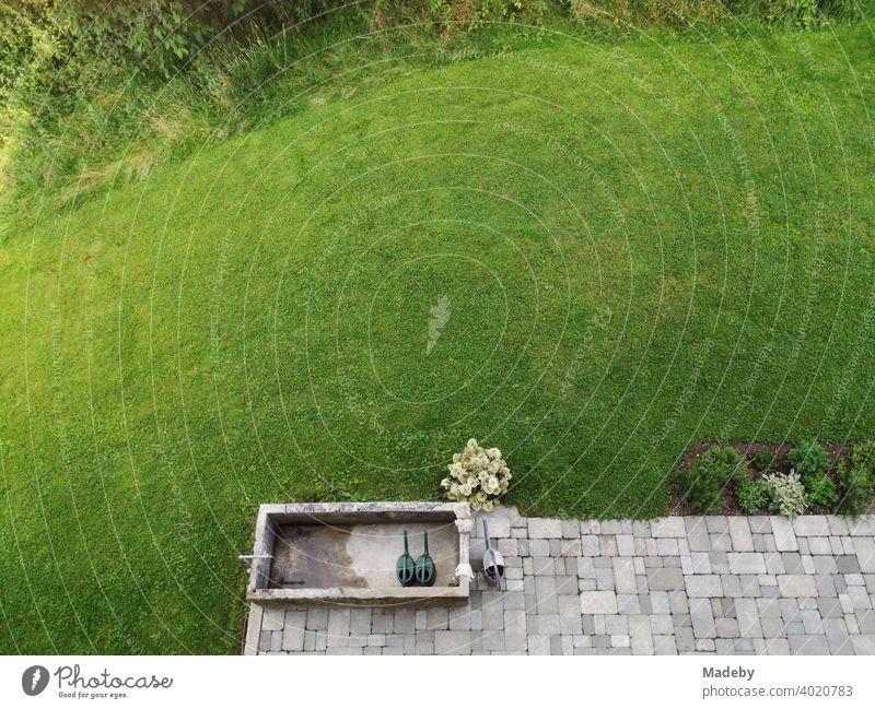 Grau gepflasterte Terrasse mit alter Viehtränke und grünem Rasen vor einem Bauernhaus in Rudersau bei Rottenbuch im Kreis Weilheim-Schongau in Oberbayern Wiese