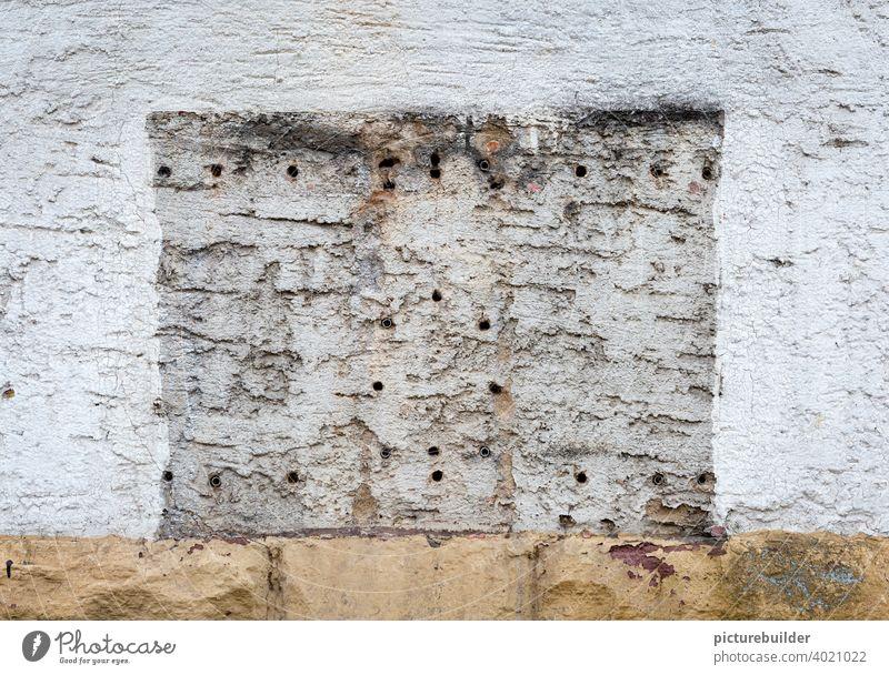 Hauswand mit Bohrlöchern und Umriss eines Kaugummiautomaten Wand Mauer Häuserwand Löcher Bohrungen Wandfarbe Farbe weiß Sockel Außenaufnahme Fassade Farbfoto