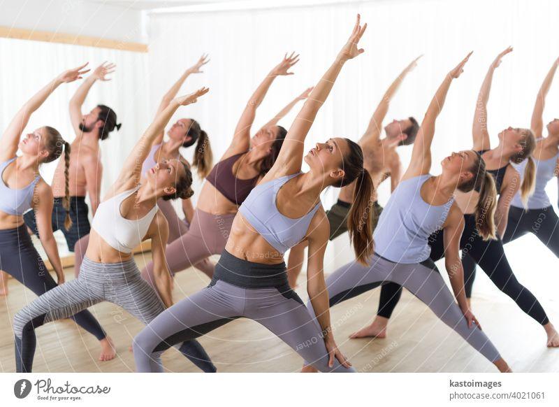 Gruppe junger, authentischer, sportlicher, attraktiver Menschen im Yogastudio, die eine Yogastunde mit einem Lehrer praktizieren. Gesunder aktiver Lebensstil, Training im Fitnessstudio