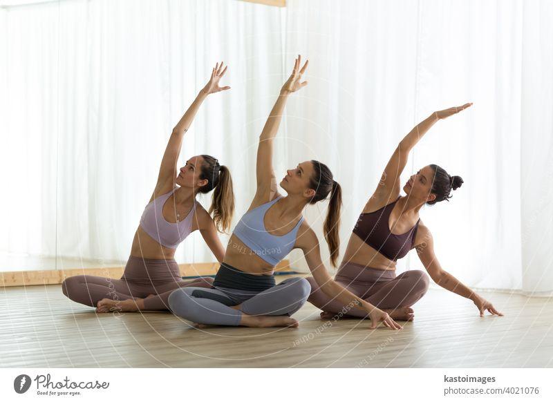 Gruppe junger, sportlicher, attraktiver Frauen, die eine Yogastunde mit einem Lehrer in einem modernen, hellen Yogastudio absolvieren. Gesunder, aktiver Lebensstil, drinnen im Fitnessstudio trainieren.