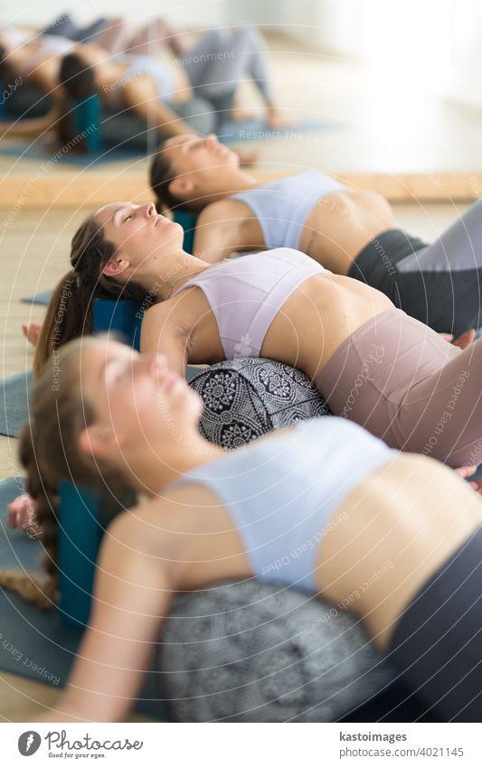 Restorative Yoga mit einem Bolster. Gruppe von drei jungen, sportlichen, attraktiven Frauen im Yogastudio, liegend auf einem Bolster-Kissen, dehnend und entspannend während Restorative Yoga. Gesunder aktiver Lebensstil