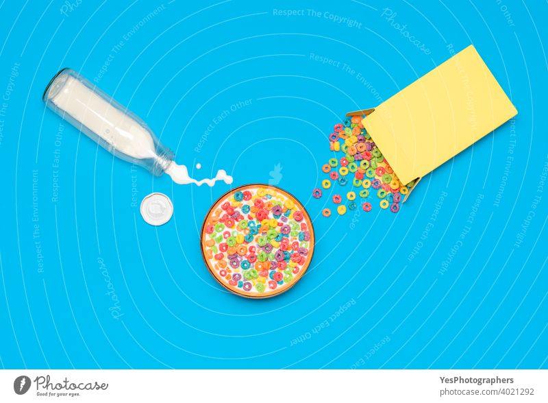 Müslischale mit Milch, Ansicht von oben. Frühstück mit buntem Müsli und Milch. obere Ansicht Hintergrund blau Flasche Schalen & Schüsseln Müslischachtel