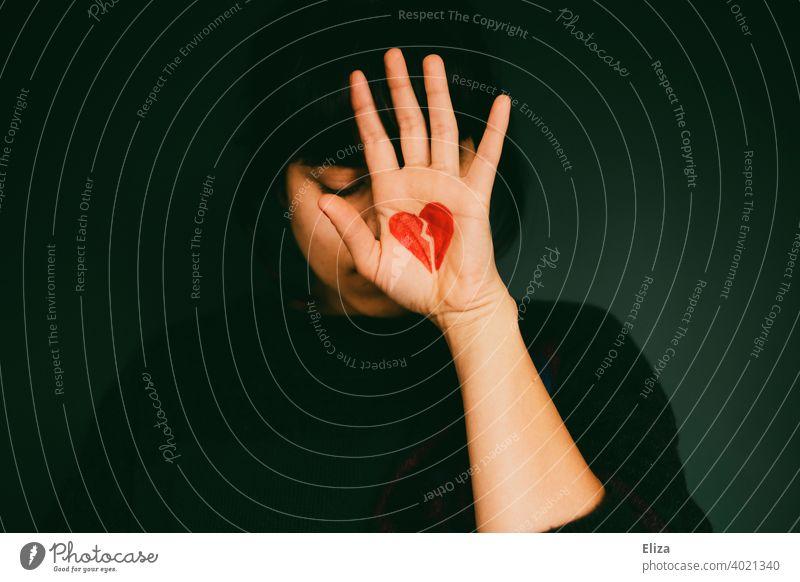 Frau hält sich die Hand, auf die ein zerbrochenes Herz gemalt ist, vor das Gesicht. Konzept Trennung und Liebeskummer. Schluss machen Beziehung Gefühle