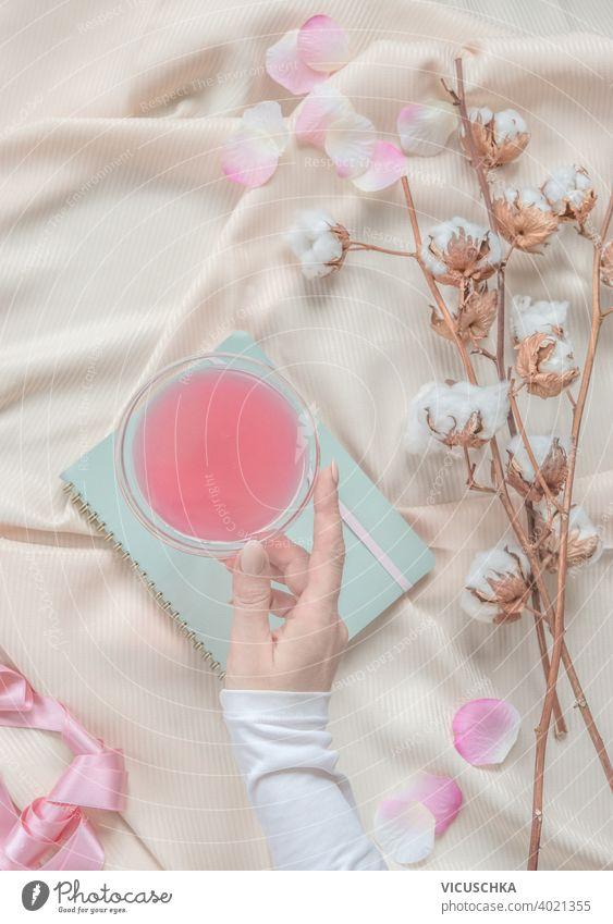 Schönheit ästhetischen Lebensstil mit Frauen Hand hält Cocktail-Glas auf beige Stoff Hintergrund mit Baumwolle Zweige und rosa Blütenblätter. Ansicht von oben