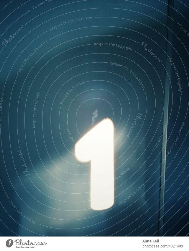 Die Nummer 1, von der Sonne an die Wand gemalt. Zahl Ziffern & Zahlen Zeichen Farbfoto Menschenleer licht Schatten Innenaufnahme weiß