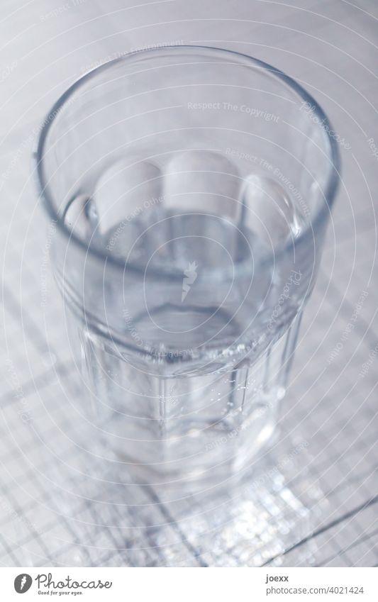 Glas Wasser, halbvoll, auf glänzender Oberfläche trinken Durst Wasserglas Trinkglas Gefäß Flüssigkeit Gesundheit Ernährung Maßvoll frisch Farbfoto