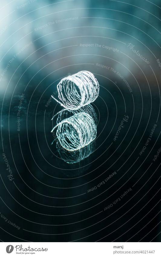 Stilsicher präsentiert sich dieser Kringel in der spiegelnden Oberfläche. Skuril verdreht verwirrend gestörte Wahrnehmung Industriefotografie verlaufend Spirale
