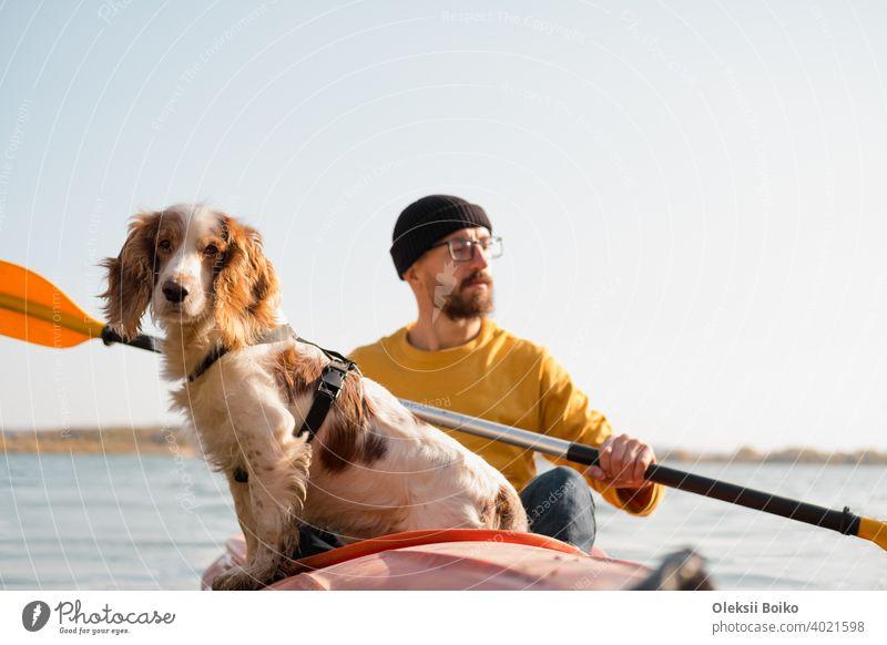 Mann mit einem Hund in einem Kanu auf dem See. Junge männliche Person mit Spaniel in einem Kajak Ruderboot, aktive Freizeit mit Haustieren, Geselligkeit, Abenteuer Hunde