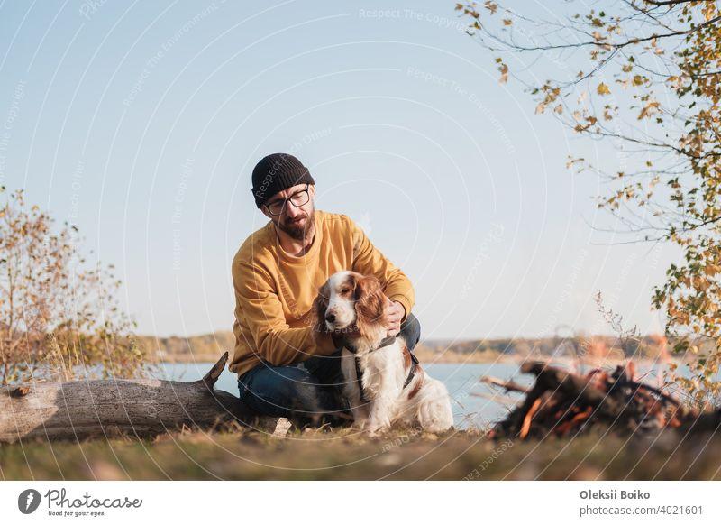 Mann umarmt seinen Hund, der am See sitzt. Aktive Erholung mit Haustieren, auf Abenteuer gehen, Kameradschaft: Spaniel-Hund und sein Besitzer sitzen im Freien