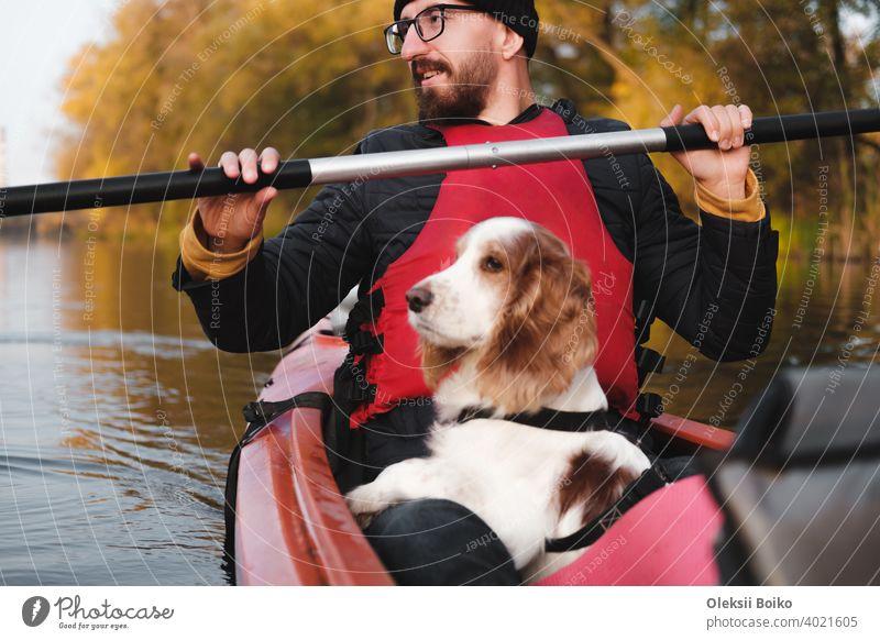 Glücklicher Mann rudert ein Kanu mit seinem Spaniel Hund, sonniges Herbstwetter. Going Kajak Bootfahren mit Hunden auf dem Fluss, aktive Haustiere, gesunde Hund und Besitzer auf ein Abenteuer