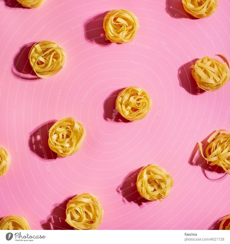 Pasta Kunst mit Tagliatelle auf rosa Hintergrund Spätzle Muster kreativ Layout Top Ansicht flach legen Quadrat Ernte Draufsicht flache Verlegung