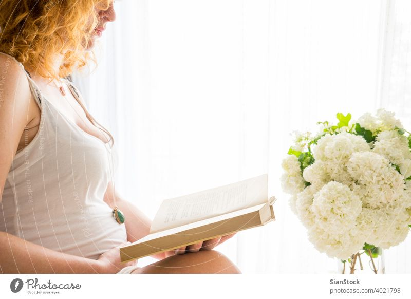 Schwangere Frau, die ihren Bauch berührt, während sie ein Buch liest schwanger Bett Schwangerschaft lesen Rotschopf rote Haare Morgen jung Mädchen Fenster