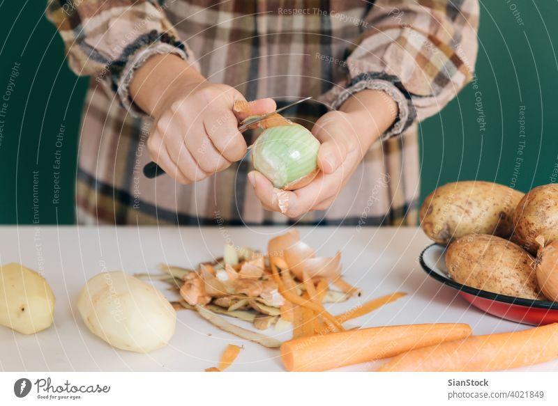 Frau schält in ihrer Küche auf weißem Marmor Zwiebeln ab, um ihr Essen zuzubereiten. sich[Akk] schälen Gemüse Kartoffeln Veganer heimwärts peel-off angeblättert
