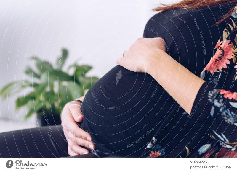 Nahaufnahme einer jungen schwangeren Frau, die ihren Bauch berührt Schwangerschaft schön Glück Leben heimwärts Mutterschaft Pflege Baby Konzept Pflanzen