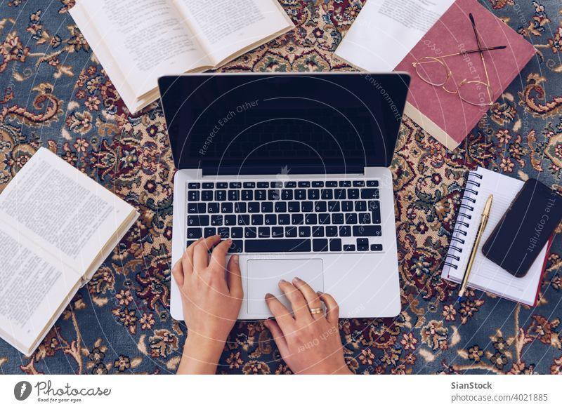 Junge Frau liegt auf dem Teppich und studiert zu Hause. arbeiten Lügen schreibend Buch Schreibstift Bücher lesen Hände Hausaufgabe Brille jung Mädchen Kaukasier