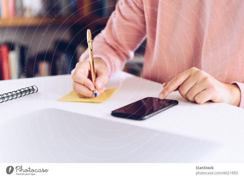 Junge Frau benutzt ein Mobiltelefon, während sie zu Hause mit einem Laptop arbeitet. Business heimwärts Technik & Technologie klug Telefon Computer Schreibtisch