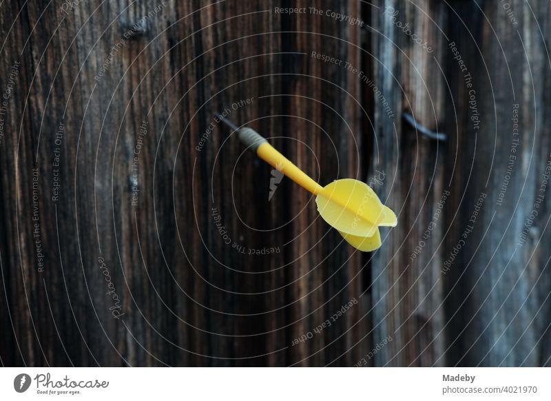 Gelber Dartpfeil im braunen Holz einer alten Scheune auf einem Bauernhof in Rudersau bei Rottenbuch im Kreis Weilheim-Schongau in Oberbayern Pfeil Spiel