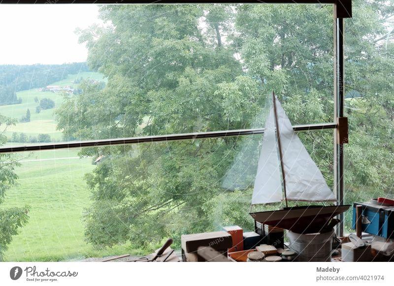 Segelschiff für Kimder mit weißen Segeln auf einer Werkbank in einem alten Bauernhaus mit Blick auf Wiesen und Felder in Rudersau bei Rottenbuch im Kreis Weilheim-Schongau in Oberbayern