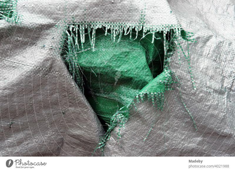 Aufgerissene Kunststoffplane mit Fasern in Grau und Grün in einem Garten in Rudersau bei Rottenbuch im Kreis Weilheim-Schongau in Oberbayern Plane Abdeckung