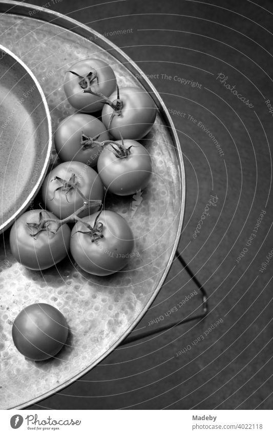 Frische Tomaten neben einer Schale auf einem dekorativen runden Tablett mit Füßen in einer Designerwohnung in Rudersau bei Rottenbuch im Kreis Weilheim-Schongau in Oberbayern, fotografiert in klassischem Schwarzweiß