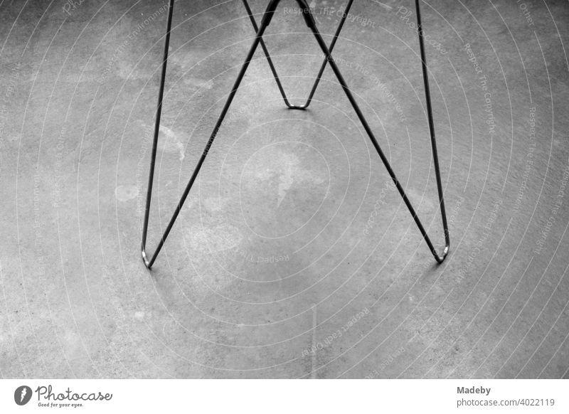 Drahtgestell als Füße eines Beistelltisch auf grauem Betonboden in einer Designerwohnung in Rudersau bei Rottenbuch im Kreis Weilheim-Schongau in Oberbayern, fotografiert in klassischem Schwarzweiß