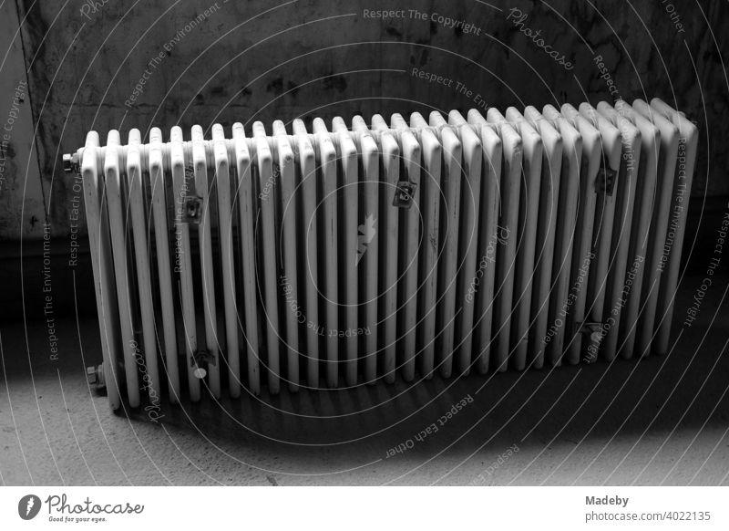 Ausrangierter traditioneller Heizkörper im dunklen Keller eines Bauernhaus in Rudersau bei Rottenbuch im Kreis Weilheim-Schongau in Oberbayern, fotografiert in klassischem Schwarzweiß