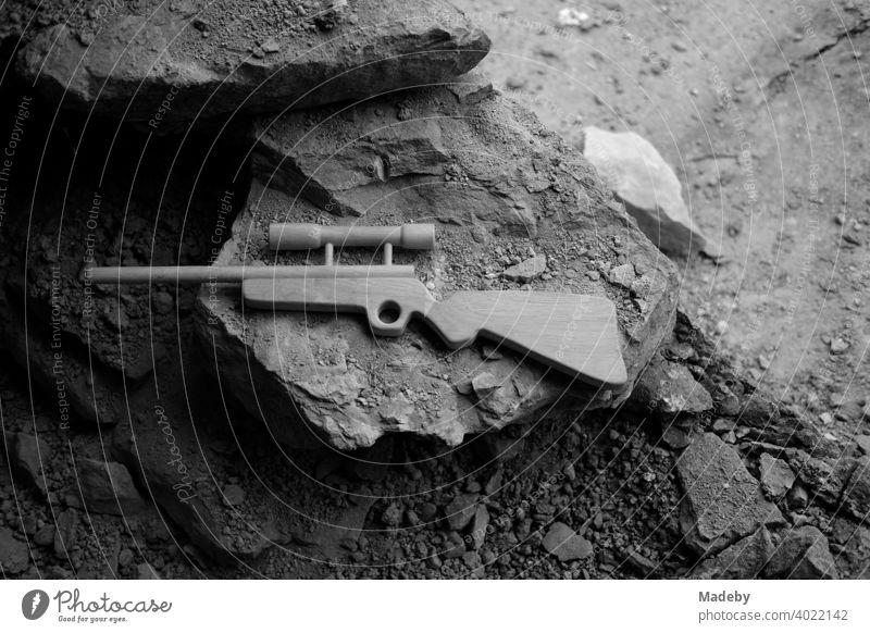 Spielzeuggewehr aus Holz mit Zielfernrohr auf zerbröselndem Gestein einem alten Bauernhaus in Rudersau bei Rottenbuch im Kreis Weilheim-Schongau in Oberbayern, fotografiert in klassischem Schwarzweiß