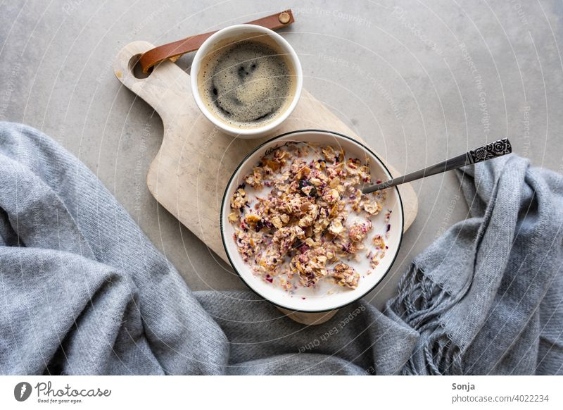 Müsli mit Milch in einer Schüssel und eine Tasse Kaffee. Gesundes Frühstück. Schalen & Schüsseln Schneidebrett Holz Porridge Gesunde Ernährung rustikal Vitamin
