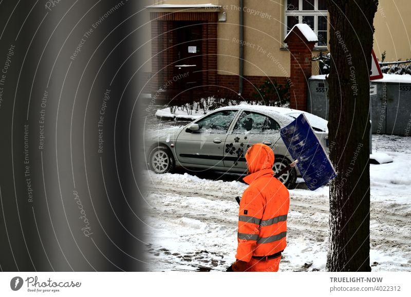 Mensch in Signal orange farbenem Overall mit Kapuze geht in kleiner Wohnstraße vorbei,  Schneeschieber lässig über der Schulter. Hauseingang, Auto, Baum als Kulisse. Schnee liegt noch überall. Tauwetter erledigt den Rest, mag er denken.