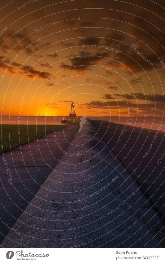 Quermarkenfeuer auf einer Mole bei Sonnenuntergangs-Himmel in der Nähe von Wilhelmshaven leuchtfeuer leuchtturm quermarkenfeuer mauer maritim seefahrt